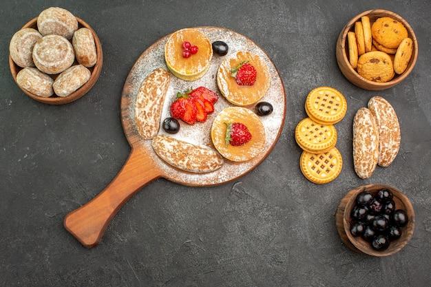 Bovenaanzicht smakelijke pannenkoeken met zoete taarten en fruit op donkere ondergrond suikertaart dessert