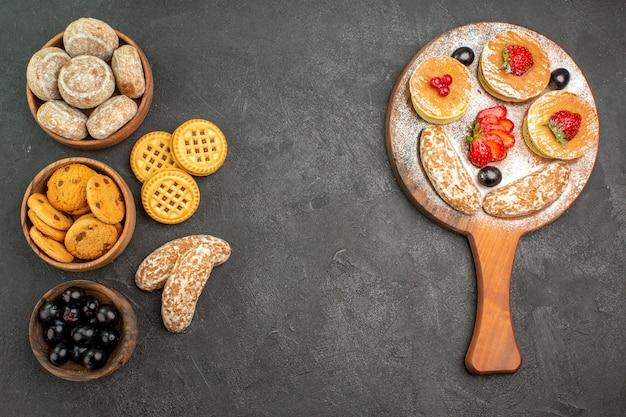Bovenaanzicht smakelijke pannenkoeken met zoete taarten en fruit op donkere ondergrond zoete cake dessert