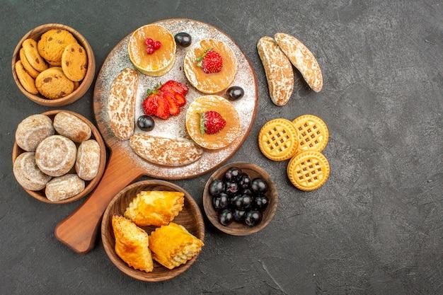 Bovenaanzicht smakelijke pannenkoeken met zoete taarten en fruit op donkere vloer