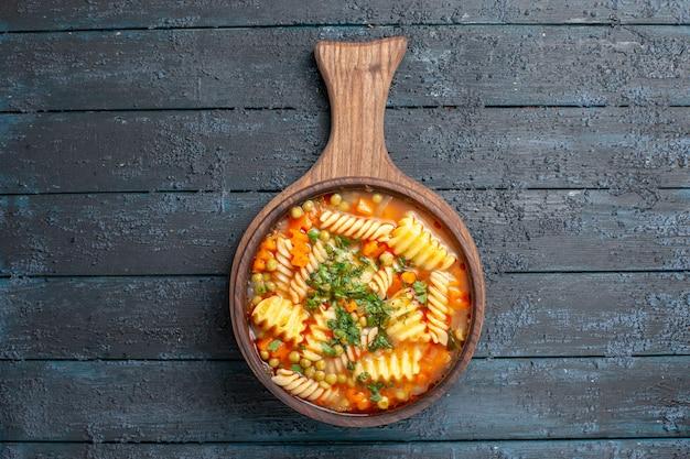 Bovenaanzicht smakelijke pastasoep van spiraalvormige italiaanse pasta met greens op donkerblauwe bureaukeukenschotel italiaanse pastasoepkleur