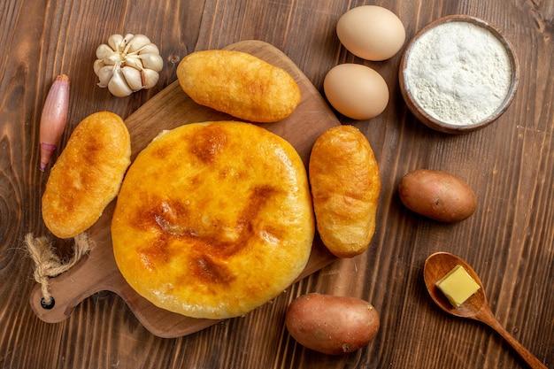 Bovenaanzicht smakelijke pompoentaart met aardappel hotcakes op bruine houten vloer taart taart hotcake bakoven