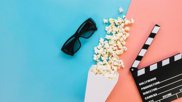 Bovenaanzicht smakelijke popcorndoos met filmklapper