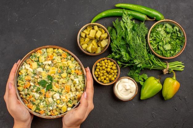 Bovenaanzicht smakelijke salade met groenen op donkere achtergrond