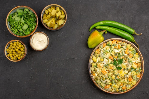 Bovenaanzicht smakelijke salade met ingrediënten op donkere achtergrond