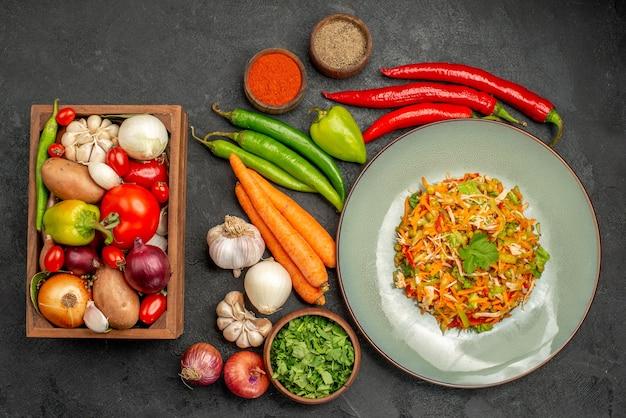 Bovenaanzicht smakelijke salade met verse groenten op grijze voedseldieetsalade