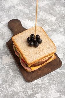 Bovenaanzicht smakelijke sandwich met olijfham tomaten groenten op stok op de lichte achtergrond sandwich eten snack ontbijt foto