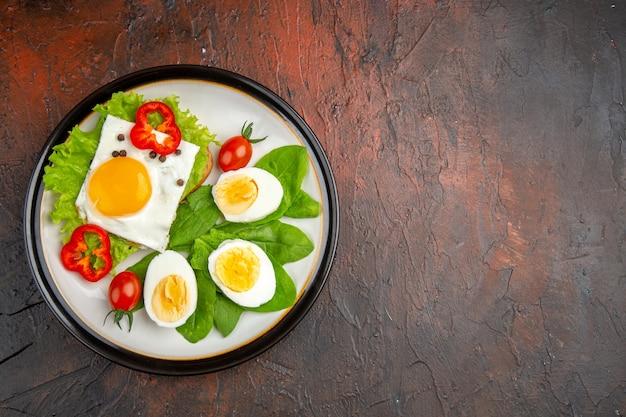 Bovenaanzicht smakelijke sandwich met roerei en gekookte eieren en salade binnen plaat op donkere tafel