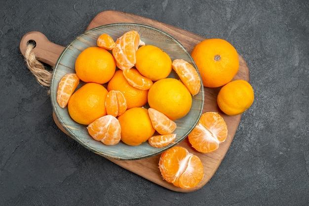 Bovenaanzicht smakelijke sappige mandarijnen binnen plaat op grijze achtergrond