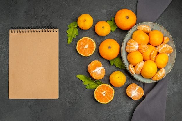 Bovenaanzicht smakelijke sappige mandarijnen in plaat op donkere achtergrond