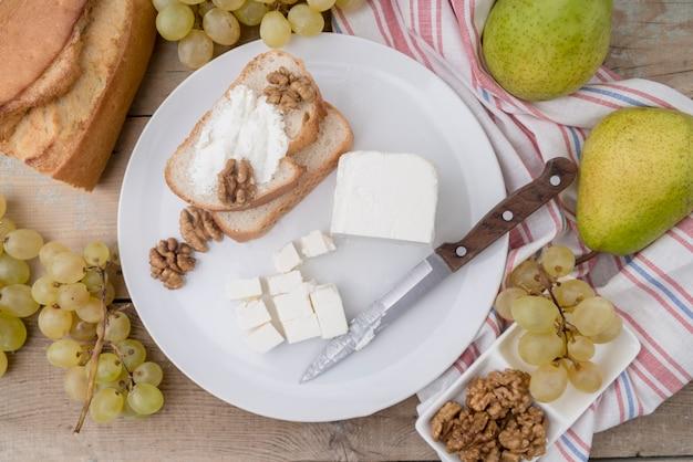 Bovenaanzicht smakelijke selectie van fruit met kaas en brood
