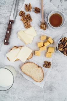 Bovenaanzicht smakelijke selectie van kaas met honing en brood