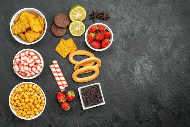 Bovenaanzicht smakelijke snacks met crakers limoen en sappige aardbeien cacaobloem kerstmissuikergoed op een donkere achtergrond met vrije ruimte