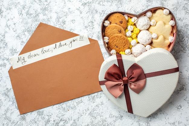 Bovenaanzicht smakelijke snoepjes, koekjes, koekjes en snoepjes in een hartvormige doos op een witte oppervlakte, suikertaartthee, zoete, lekkere cake