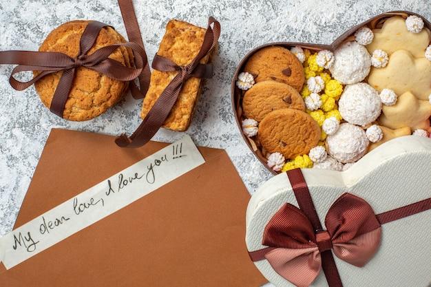 Bovenaanzicht smakelijke snoepjes, koekjes, koekjes en snoepjes in hartvormige doos op witte oppervlakte suikertaart thee zoete cake