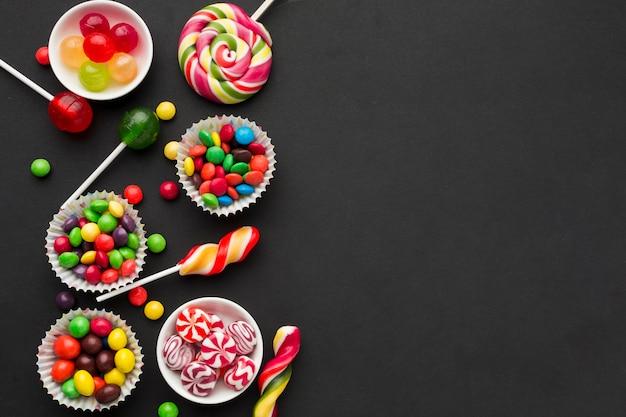 Bovenaanzicht smakelijke snoepjes op zwarte tafel