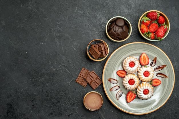Bovenaanzicht smakelijke snoepkoekjes met aardbeien- en chocoladesaus naast kommen aardbeienchocolade en saus op donkere tafel
