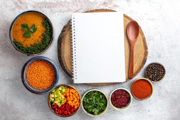 Bovenaanzicht smakelijke soep gekookte bonensoep met kruiden op wit bureau groenten maaltijd eten soepboon