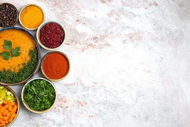 Bovenaanzicht smakelijke soep met greens en verschillende kruiden op de witte groente van de het voedselsoep van de bureaumaaltijd