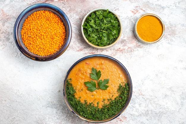 Bovenaanzicht smakelijke soep met greens op de witte soepgroenten van het oppervlaktemaaltijdvoedsel Gratis Foto