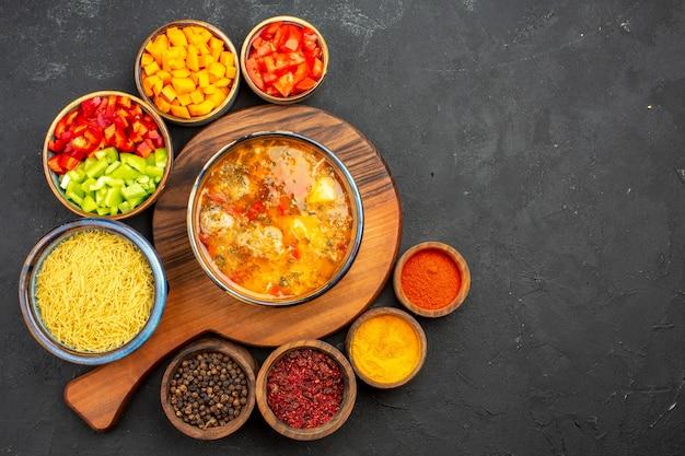 Bovenaanzicht smakelijke soep met verschillende kruiden en gesneden peper op grijze achtergrond soep, maaltijd, vlees, kruiden, kruidig