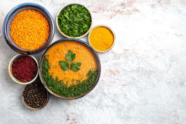 Bovenaanzicht smakelijke soep met verschillende kruiden en groenten op de witte soepgroenten van het oppervlakmaaltijdvoedsel Gratis Foto