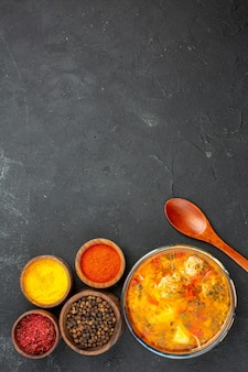 Bovenaanzicht smakelijke soep met verschillende kruiden op de grijze achtergrond soep, maaltijd, vlees, kruiden, kruidig