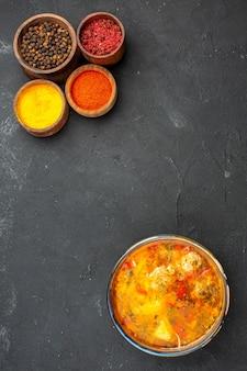 Bovenaanzicht smakelijke soep met verschillende kruiden op grijs bureau soep maaltijd vlees kruiden pittig