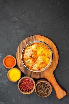 Bovenaanzicht smakelijke soep met verschillende kruiden op grijze vloer soep maaltijd eten vlees kruiden pittig