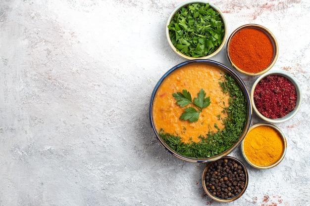 Bovenaanzicht smakelijke soep met verschillende kruiden op witte oppervlak maaltijd soepgroenten