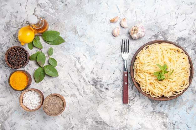 Bovenaanzicht smakelijke spaghetti met smaakmakers op de witte deegschotel pasta