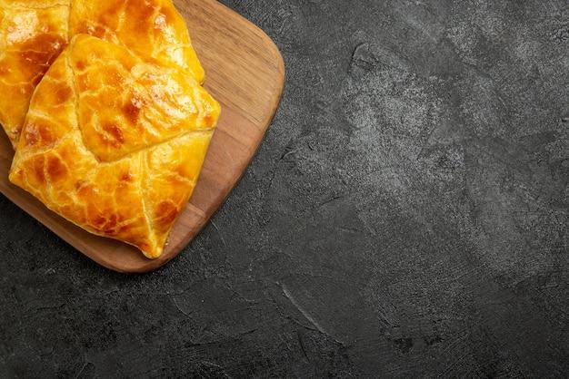 Bovenaanzicht smakelijke taarten op de snijplank en smakelijke taarten aan de linkerkant van de tafel