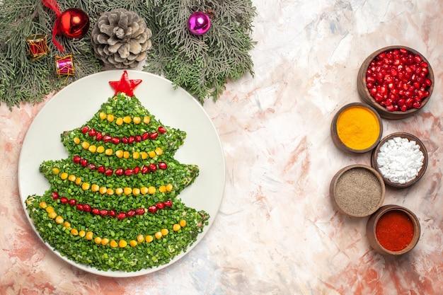 Bovenaanzicht smakelijke vakantiesalade in de vorm van de nieuwe jaarboom met kruiden op lichte achtergrond