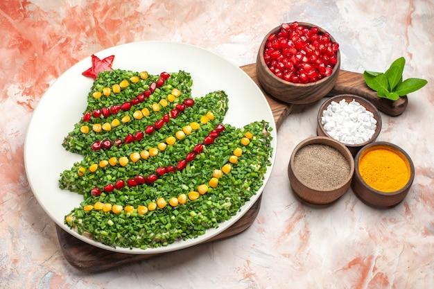 Bovenaanzicht smakelijke vakantiesalade in de vorm van de nieuwe jaarboom op de lichte achtergrond