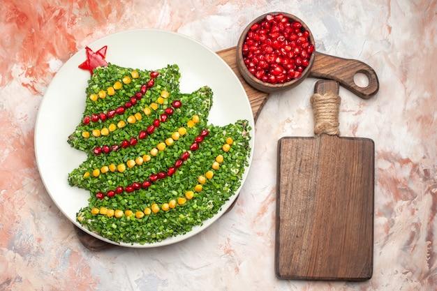 Bovenaanzicht smakelijke vakantiesalade in de vorm van de nieuwe jaarboom op licht bureau