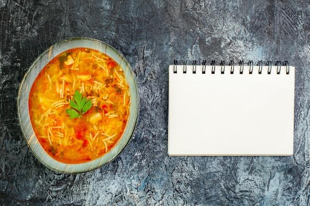 Bovenaanzicht smakelijke vermicellisoep binnen bord op de lichtgrijze tafel