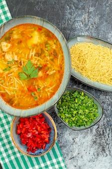 Bovenaanzicht smakelijke vermicellisoep met greens en rauwe vermicelli op lichtgrijze tafel
