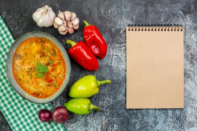 Bovenaanzicht smakelijke vermicellisoep met knoflook en groenten op lichtgrijze tafel