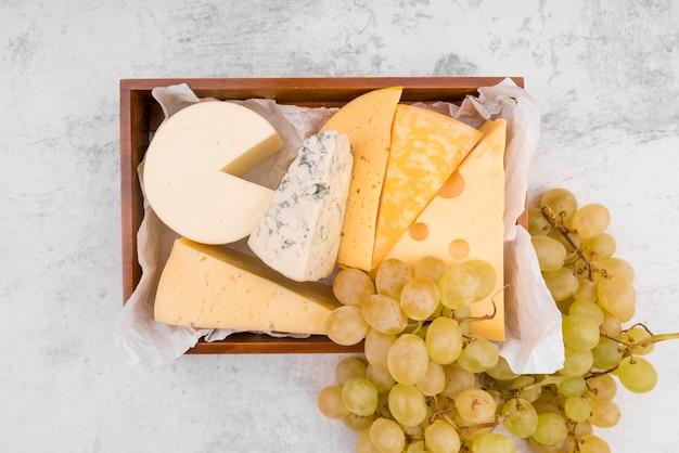 Bovenaanzicht smakelijke verscheidenheid aan kaas met druiven