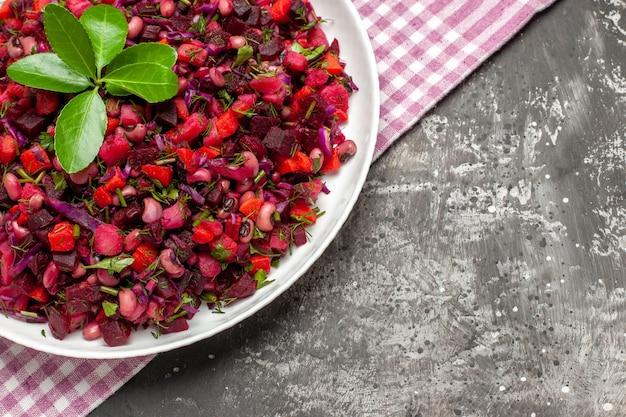 Bovenaanzicht smakelijke vinaigrette bietensalade binnen plaat op het donkere oppervlak