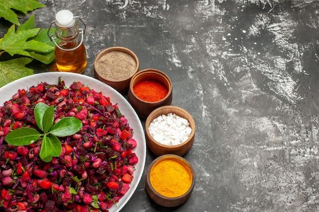 Bovenaanzicht smakelijke vinaigrette bietensalade met kruiden op donker bureau