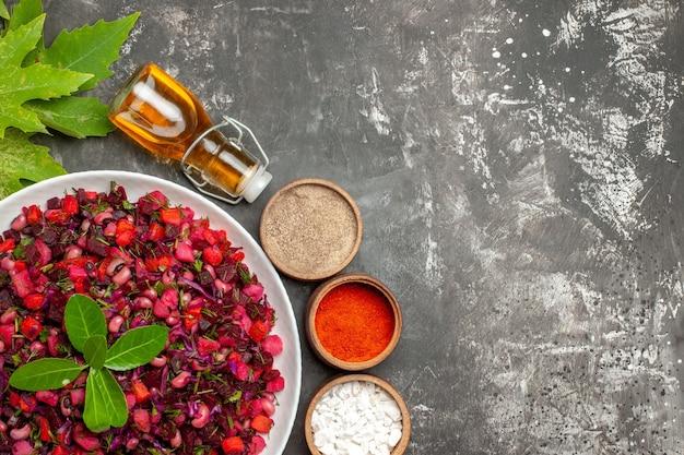 Bovenaanzicht smakelijke vinaigrette bietensalade met kruiden op het donkere oppervlak