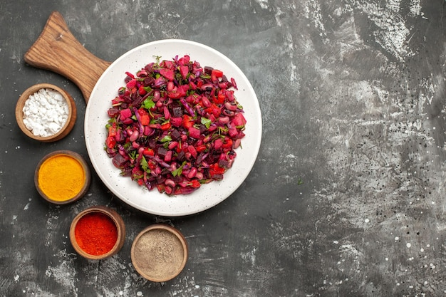 Bovenaanzicht smakelijke vinaigrette salade met kruiden op het grijze oppervlak
