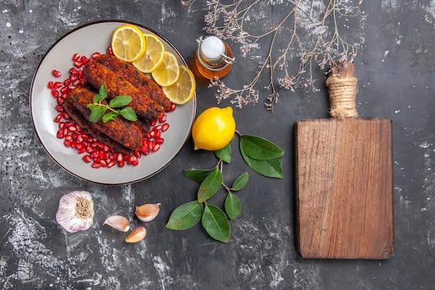 Bovenaanzicht smakelijke vleeskoteletten met citroenplakken op grijze achtergrondschotelfoto
