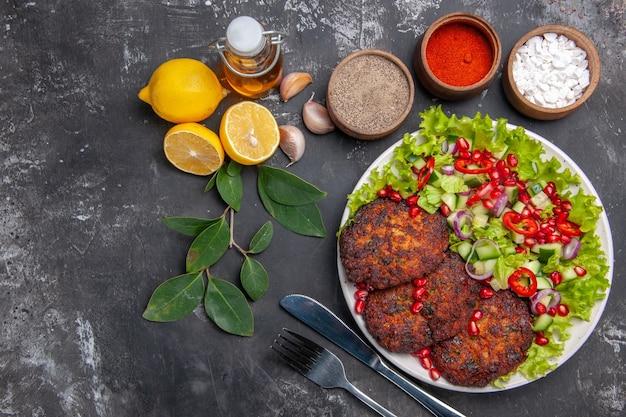 Bovenaanzicht smakelijke vleeskoteletten met groentesalade op grijze achtergrondfoto voedsel maaltijdschotel