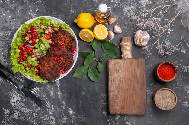 Bovenaanzicht smakelijke vleeskoteletten met groentesalade op grijze achtergrondschotelfoto voedselmaaltijd
