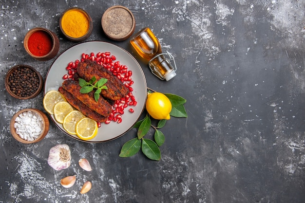 Bovenaanzicht smakelijke vleeskoteletten met kruiden op de grijze achtergrond maaltijdvoedsel schotel