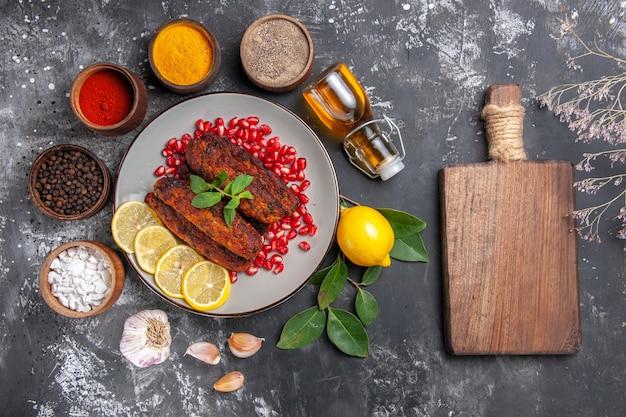 Bovenaanzicht smakelijke vleeskoteletten met kruiden op het grijze achtergrondschotelfotovoedsel