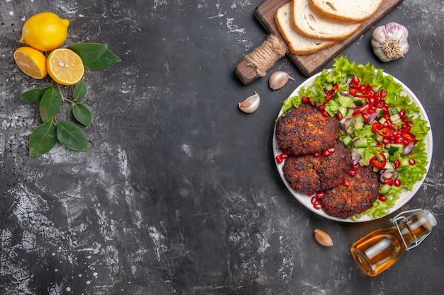 Bovenaanzicht smakelijke vleeskoteletten met salade en brood op de grijze achtergrondschotelfoto voedselmaaltijd