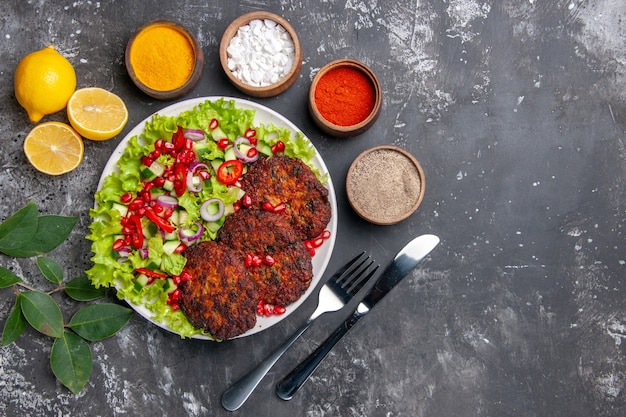 Bovenaanzicht smakelijke vleeskoteletten met salade en kruiden op een grijze achtergrondfoto voedsel schotel maaltijd