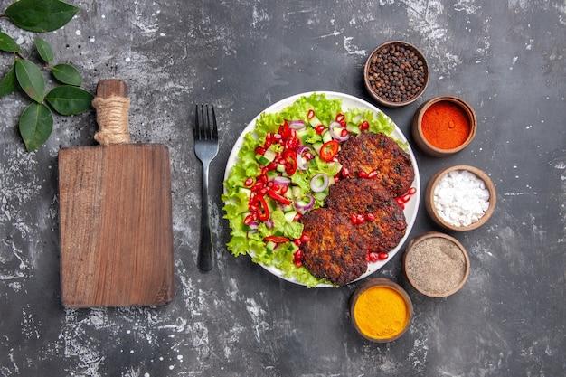 Bovenaanzicht smakelijke vleeskoteletten met salade en kruiden op grijze achtergrondfoto eten schotel vlees